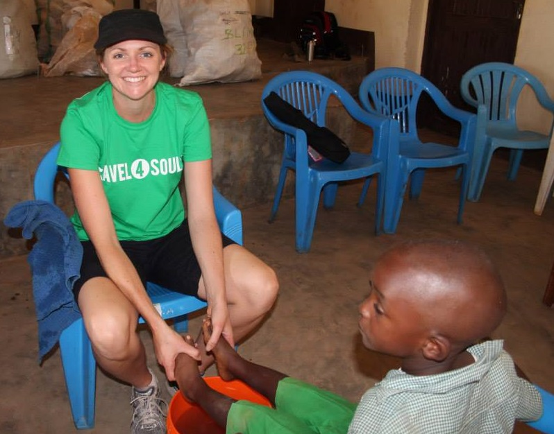 Dalice washing the feet of a young boy before fitting his new shoes, in Tanzania