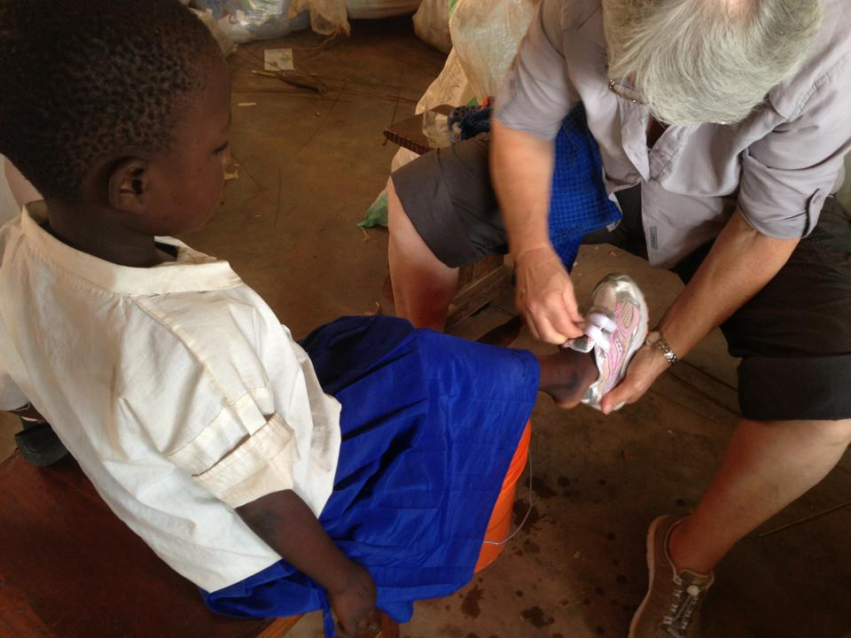 Elaine fitting shoes onto the feet of a young girl in Tanzania