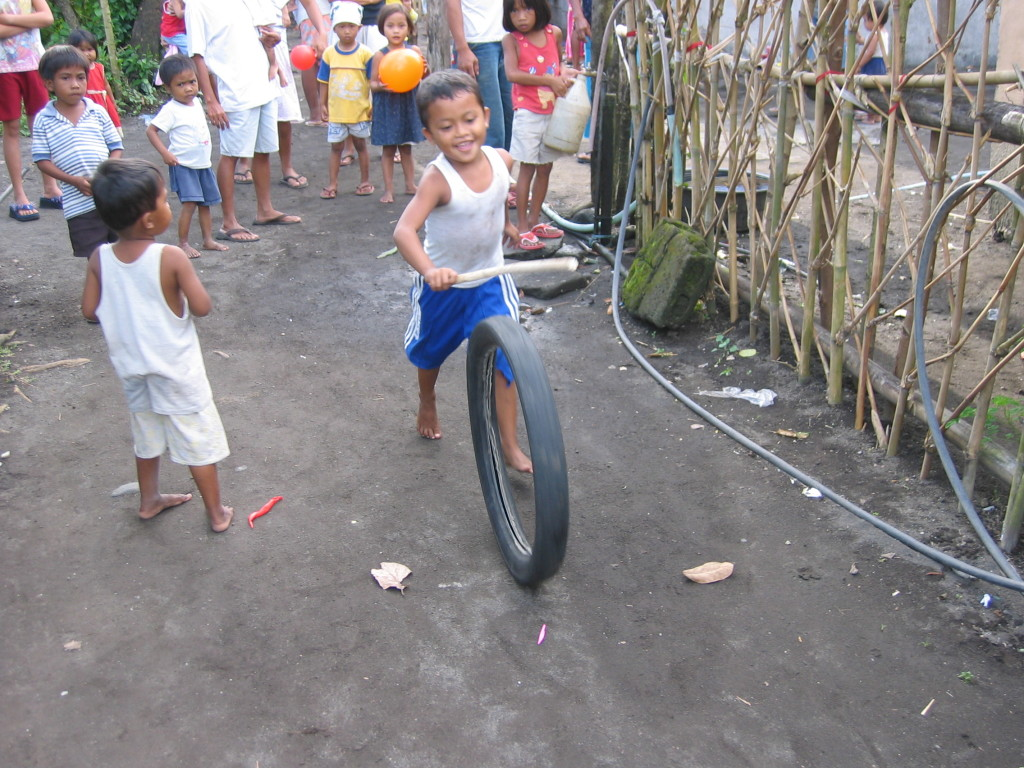 Children playing with the wheel of motor bike
