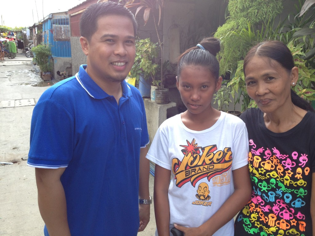 Sherwin with a sponsored child and her mother, during a community visit