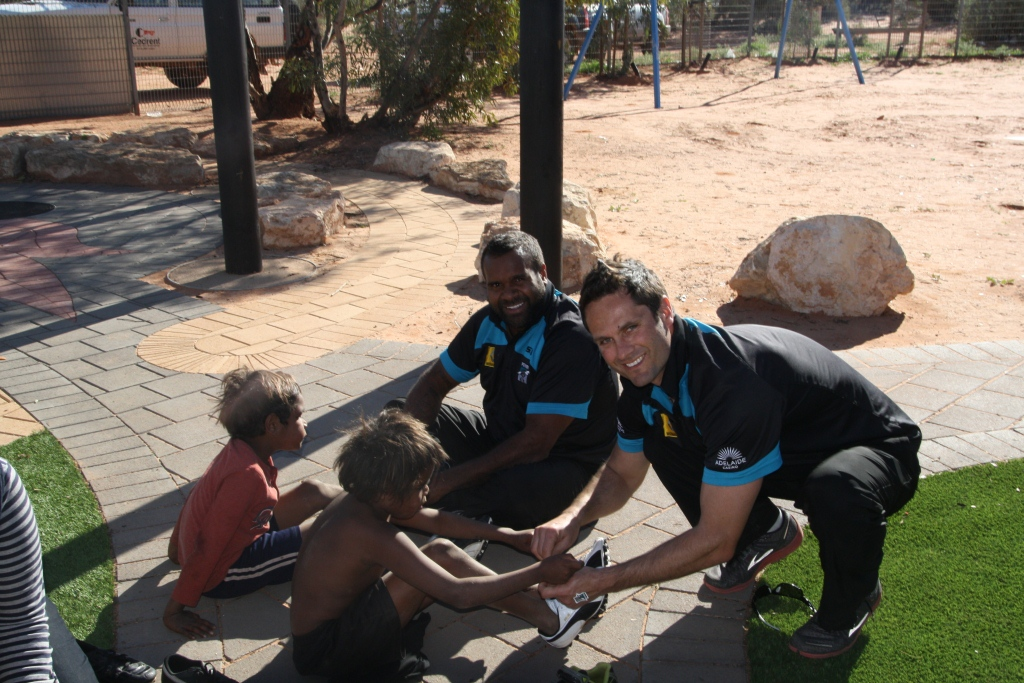 Gavin Wanganeen and Byron Pickett with Power Community Ltd. distributing boots in Oak Valley South Australia