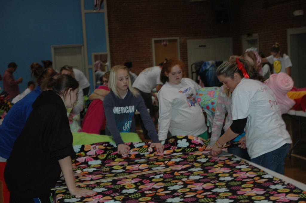 "Students of a local middle school make blankets for ""Covers for Cancer"" to go in the ""Boxes of Love""."