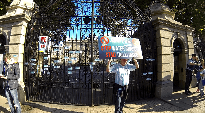 Protester holding up banners at the gates of Dail Eireann